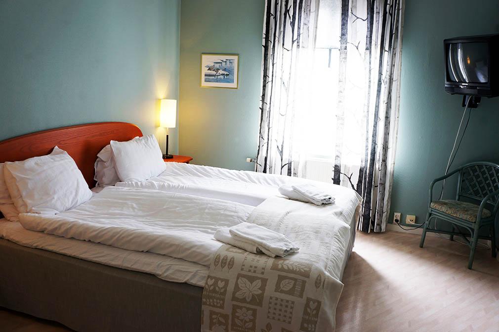 sovrum med dubbelsäng med en varm grön känsla